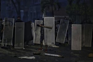 Protesters use makeshift shields during a national strike to protest against a government-proposed tax reform.