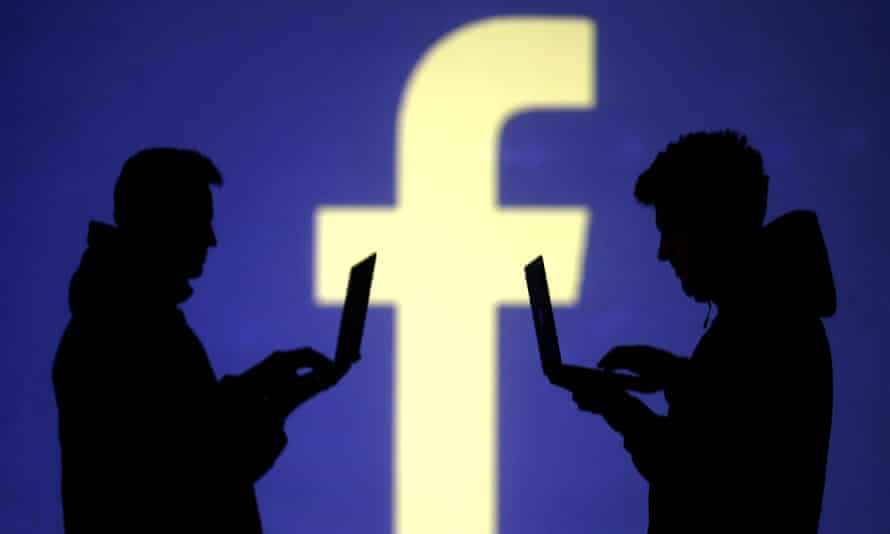 Silhouettes of laptop users are seen next to a screen projection of Facebook logo