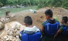 Members of Sinangoe's guardia indigena look down at the recently-discovered mining site upriver from their community.