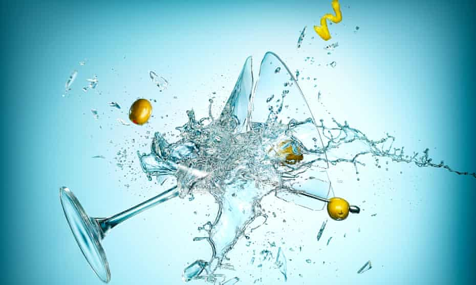 Cocktail glass, broken, in mid air with drink and decorative pieces falling, on blue background