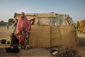 A woman and her child pose in front of their house made of cardboard in the Farm Centre Internally Displaced Persons camp in Maiduguri, Nigeria