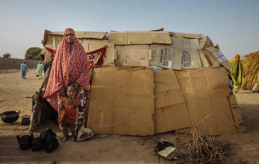 A woman and her child pose in front of their house made of cardboard in the Farm Centre Internally Displaced Persons camp in Maiduguri, Nigeria.