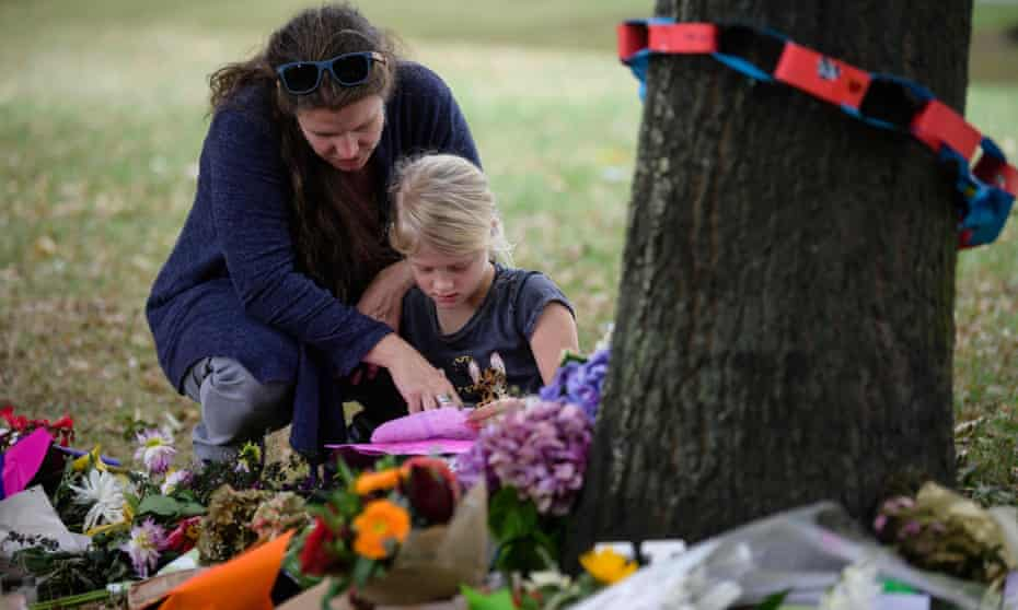 A mother and daughter look at tributes in a park outside the Al Noor Mosque in Christchurch.