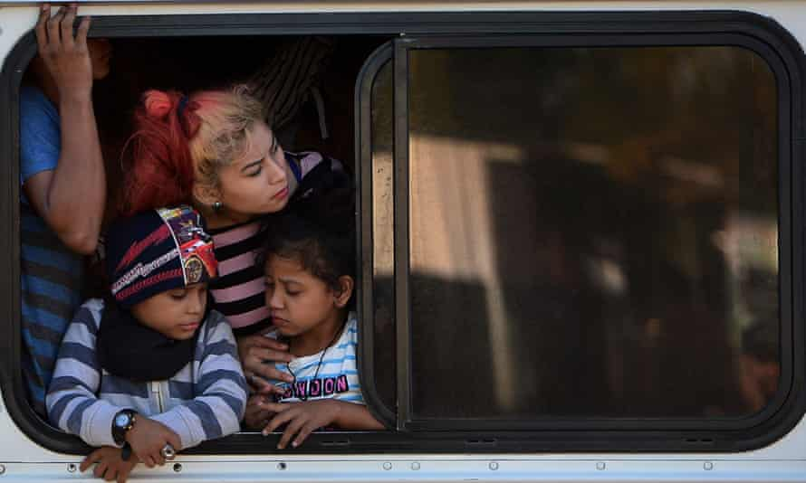 Honduran migrants look out the window of a bus as part of a caravan heading to the US on 15 January.