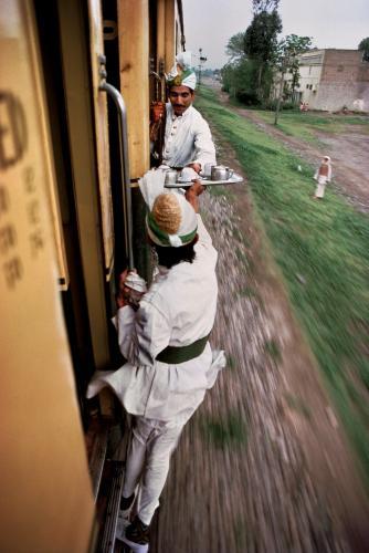 Pakistan. 1983. Breakfast Tea being passed between cars on the railway between Peshawar and Lahore.