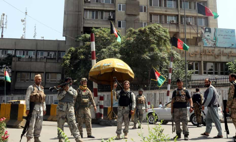 Afghan security officials stand guard at a checkpoint in Kabul