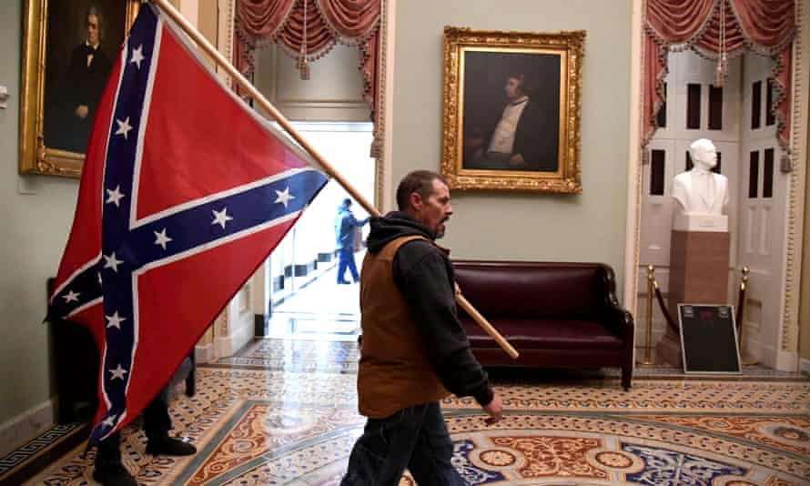 A man carries a Confederate battle flag on the second floor of the US Capitol.