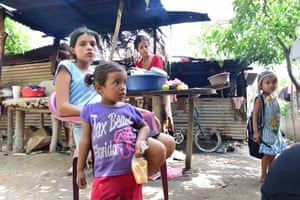 Leiva, with her two-year-old daughter in the foreground, in their small compound with other children