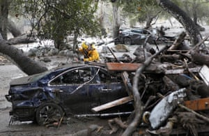 A member of the Long Beach search and rescue team looks for survivors in a car