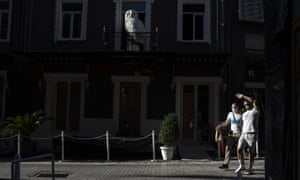 Los peatones con máscaras faciales para frenar la propagación del coronavirus caminan frente a un café cerrado, en el distrito de Psiri de Atenas, el viernes.