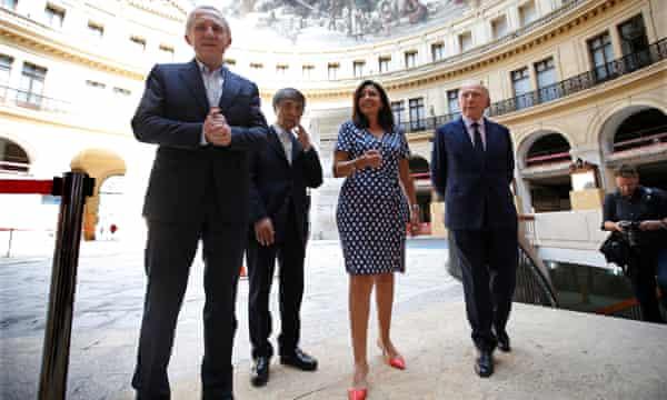 Billionaire French art collector Francois Pinault, right, Paris Mayor Anne Hidalgo, Japanese architect Tadao Ando and Francois-Henri Pinault, left, visit the Bourse de Commerce