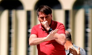 Jair Bolsonaro coughs as he speaks to supporters who were taking part in a protest against quarantine and social distancing measures to combat the coronavirus outbreak in Brasilia, Brazil