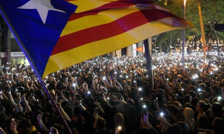 Protesters hold up their mobile phones during a demonstration in Barcelona