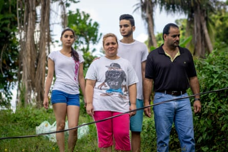 Diana Ivelisse Vera Maldonado, Jose Ruiz Gonzalez, and their children in front of their house with the disconnected power line.