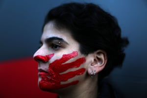 Beirut, Lebanon: a woman poses with her face painted with a red hand during a demonstration against sexual harassment, rape and domestic violence