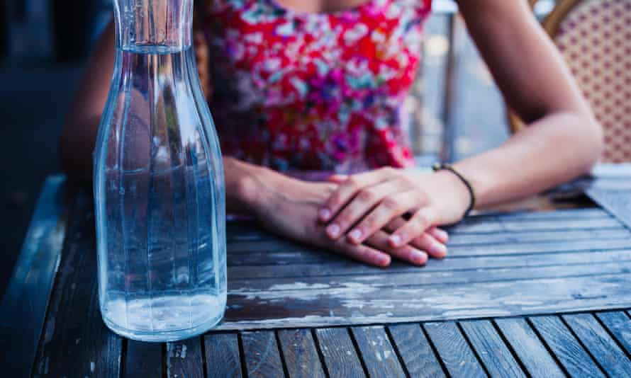A glass bottle full of tap water on an outside restaurant table. A woman sits next to it, her hands folded.