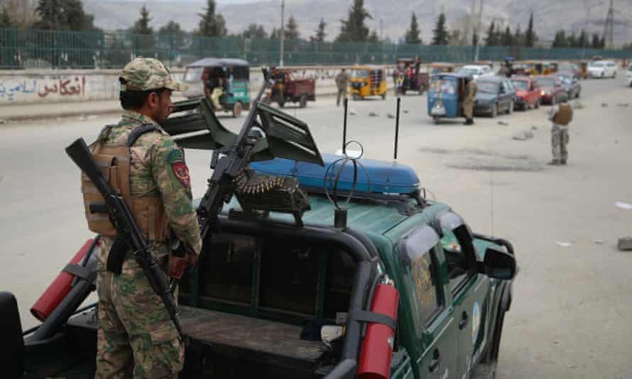 Afghan security officials check people at a checkpoint on the outskirts of Jalalabad, Afghanistan
