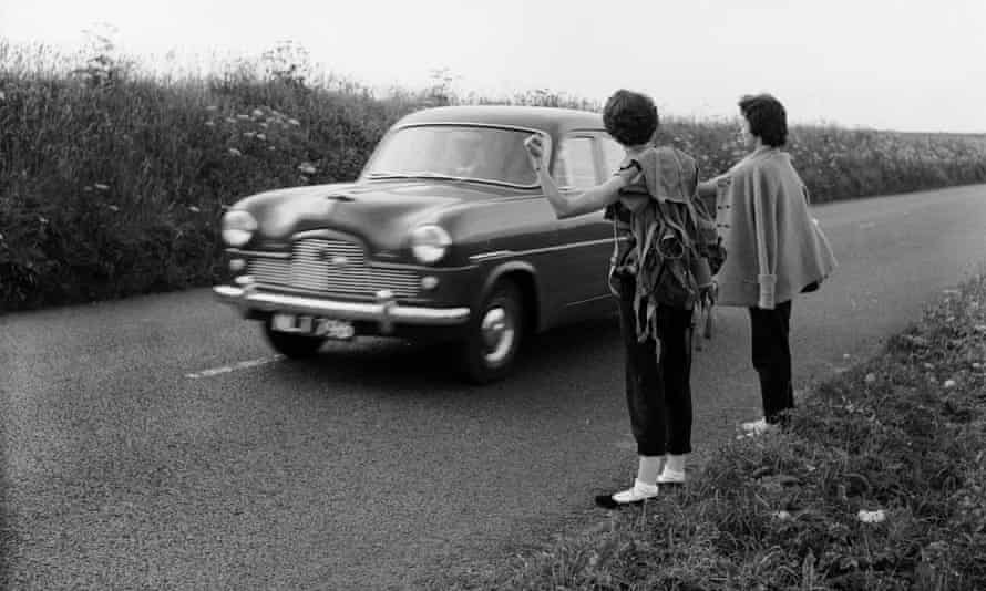 Young women hitch-hike on country lanes, 1956.
