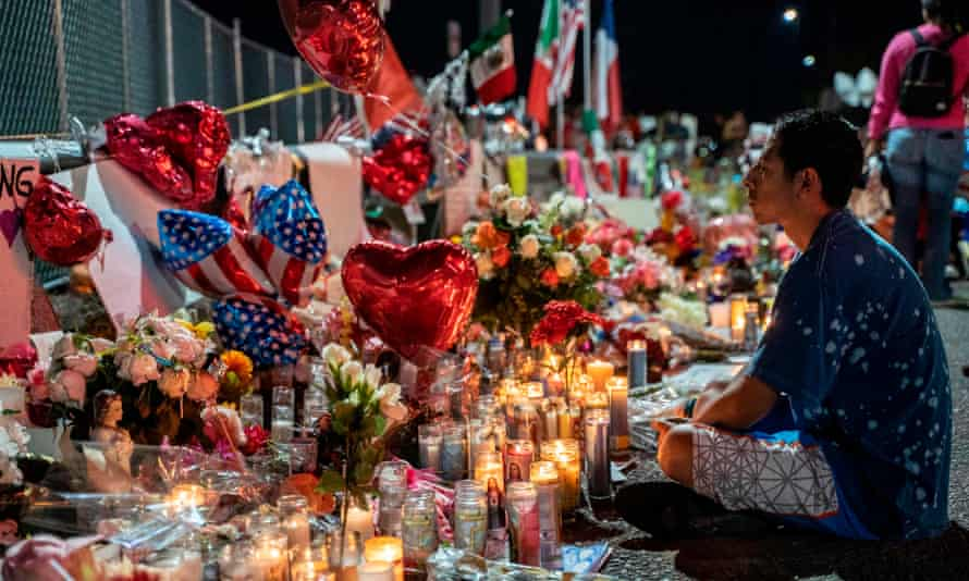 An El Paso local meditates in front of a makeshift memorial for shooting victims in El Paso, Texas, on 8 August.