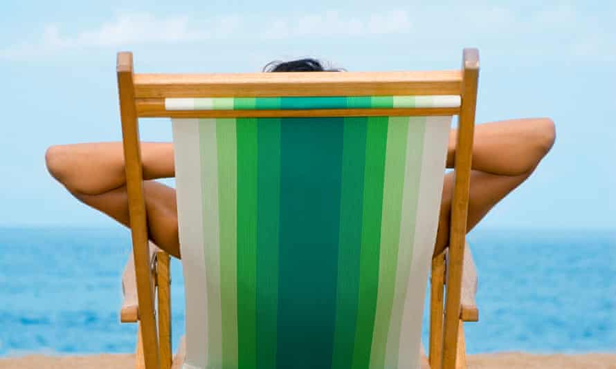 Woman in deckchair facing out to sea