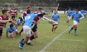 Going in for the tackle during a secondary school rugby match.