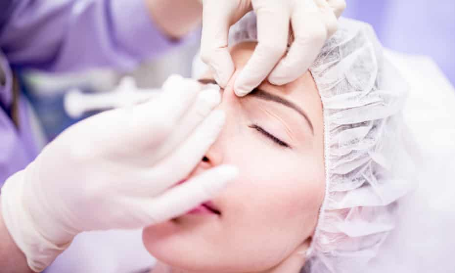 A woman is given a Botox injection
