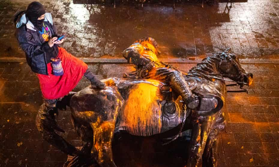 A protester stands over a toppled statue of Theodore Rosevelt during a protest Sunday in Portland, Oregon.