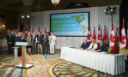 Fellow signatories applaud as Wynne signs a declaration alongside Vermont governor Peter Shumlin, right, and Quebec's premier, Philippe Couillard, center left, at the Climate Summit of the Americas meeting in Toronto on 9 July.