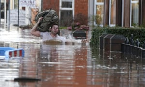 A local resident carries a bag as he wades through flood water on a residential street in Carlisle