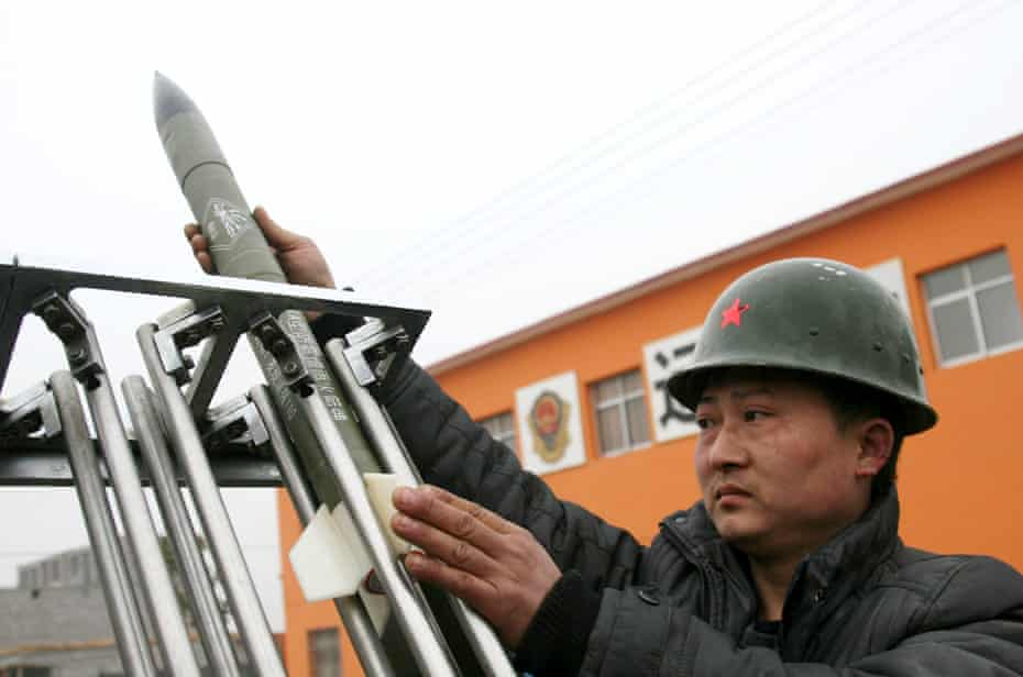 A technician at the local meteorologic department loads a cloud-seeding rocket into a launcher in drought stricken Henan Province, China.