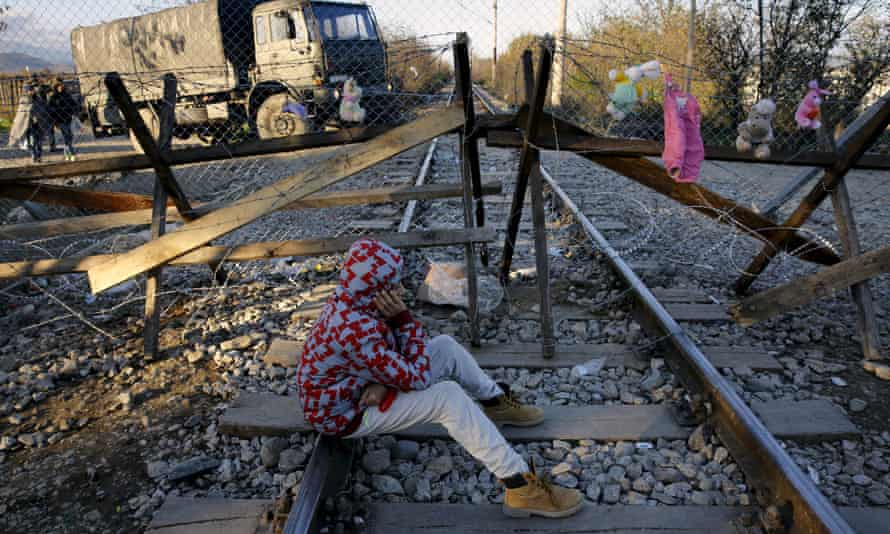 Efran, 12, a stranded Iranian migrant sits on rail tracks in front of part of a fence erected on Sunda at the Greek-Macedonian border near the Greek village of Idomeni.