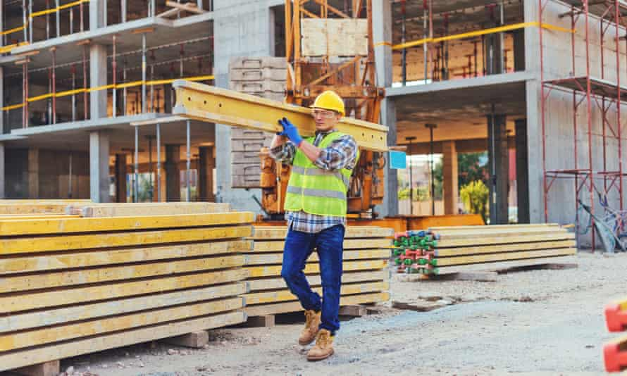 Stock image of a construction worker carrying a girder