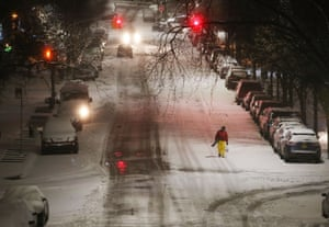 An early morning worker makes his way through the sleet and snow in New York City