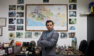 Israel Ticas in his office, standing in front of images of his team members at work and a map of El Salvador marking points of reported violent crimes.