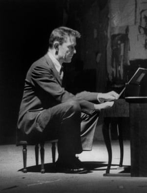 Avant-garde minimalist composer John Cage playing a children's size piano.
