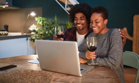 A couple drinking wine and talking to friends via a video conference