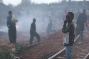 A boy stands along railroad tracks in Kibera, a slum area of Nairobi, Kenya's capital. A fire burns on the opposite side and the tracks are strewn with garbage and excrement. In May 2006, it was estimated that more than one-quarter of the city's population lives in Kibera, the largest slum in the nation, and one of the poorest and most densely populated settlements in the world.