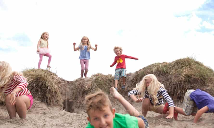 children jumping off sand dunes