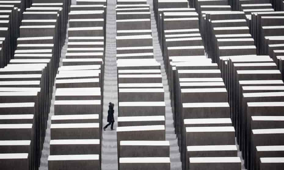 A visitor walks through the snow covered Holocaust memorial in Berlin.