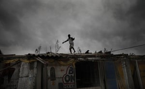 A woman inspects the roof of a shop in Bakkhali, India, after Super-cyclone Amphan made landfall near the Bay of Bengal