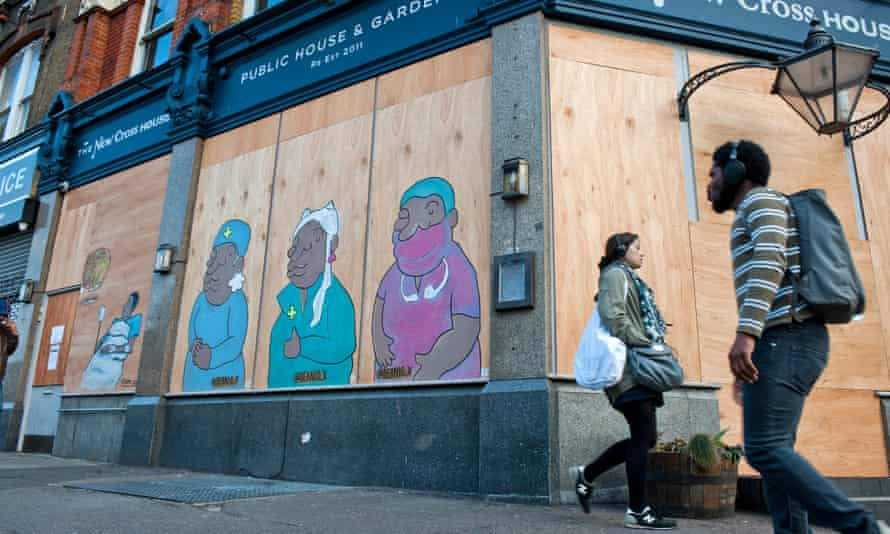 People walk past street art by Deanio X in south London in April representing how BAME NHS staff are dying at a higher rate from Covid-19