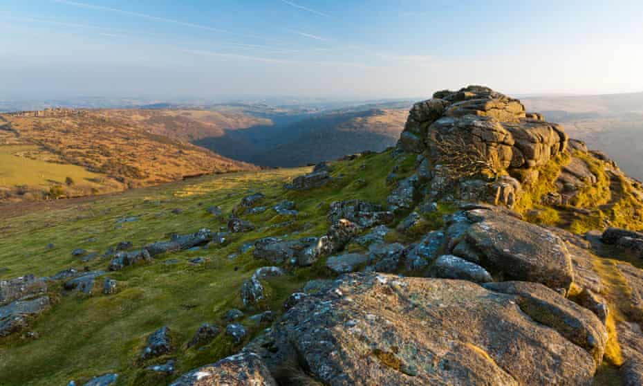 Seen on a sunny day, with a hint of mist, but blue sky is Sharp Tor, Dartmoor national park, Devon, UK