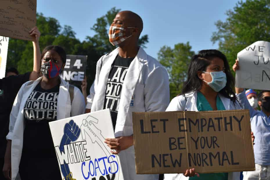 Medical workers in face masks hold signs during a rally on 6 June organised by a group named White Coats for Black Lives in Central Park.