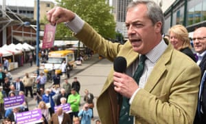 Nigel Farage campaigning in Birmingham, and holding his passport to make a point about the EU wording in it.