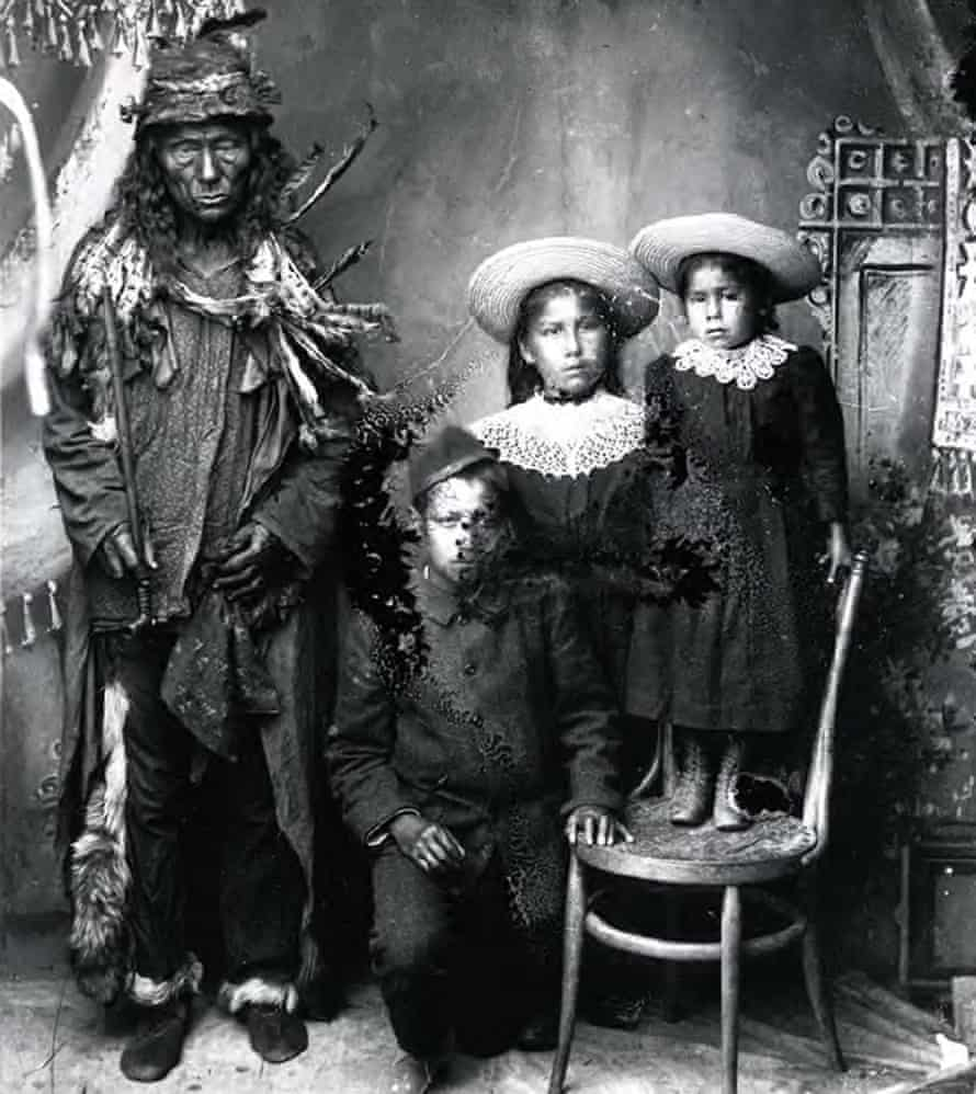 A historical photo from 1900 shows an elderly First Nations man with students at the Qu'Appelle Indian industrial school in Lebret, Northwest Territories, now Saskatchewan, Canada.