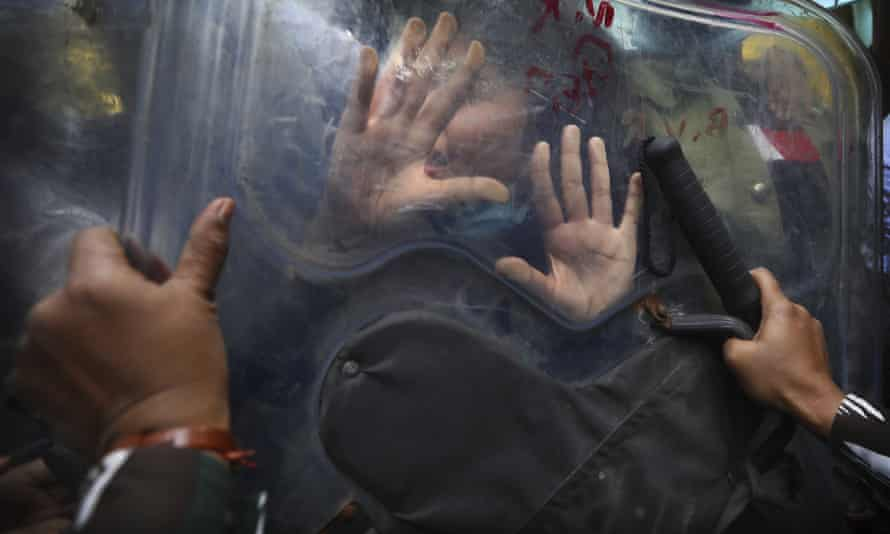 Police using riot shields push back farm-law protesters in Delhi on 3 February.