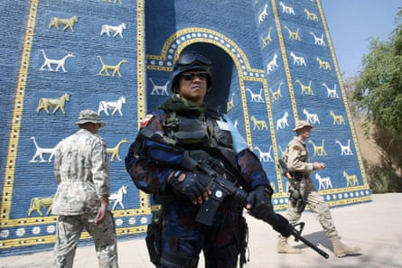 Philippine military police stand guard at the Ishtar gate as Polish and US soldiers pass by.