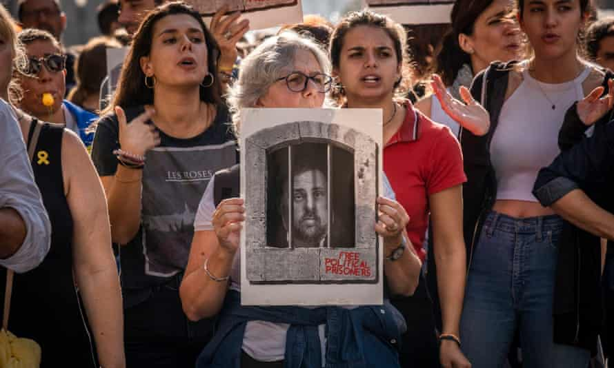 A protester in Barcelona holds a mocked-up picture of Oriol Junqueras, who has been jailed for 13 years.