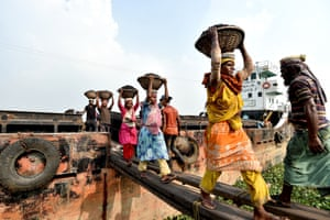 Labourers unload coal from a cargo ship in baskets on their heads in Dhaka, Bangladesh
