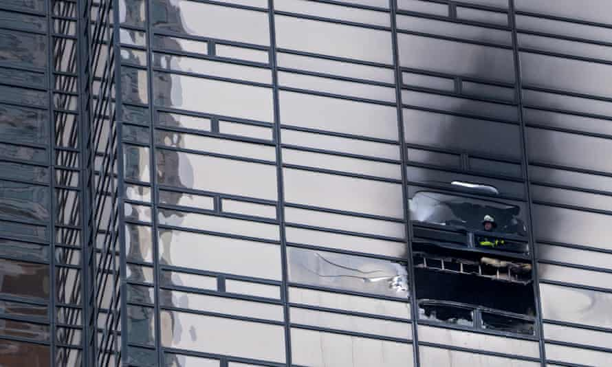 A firefighter looks out from the window of a damaged apartment in Trump Tower.